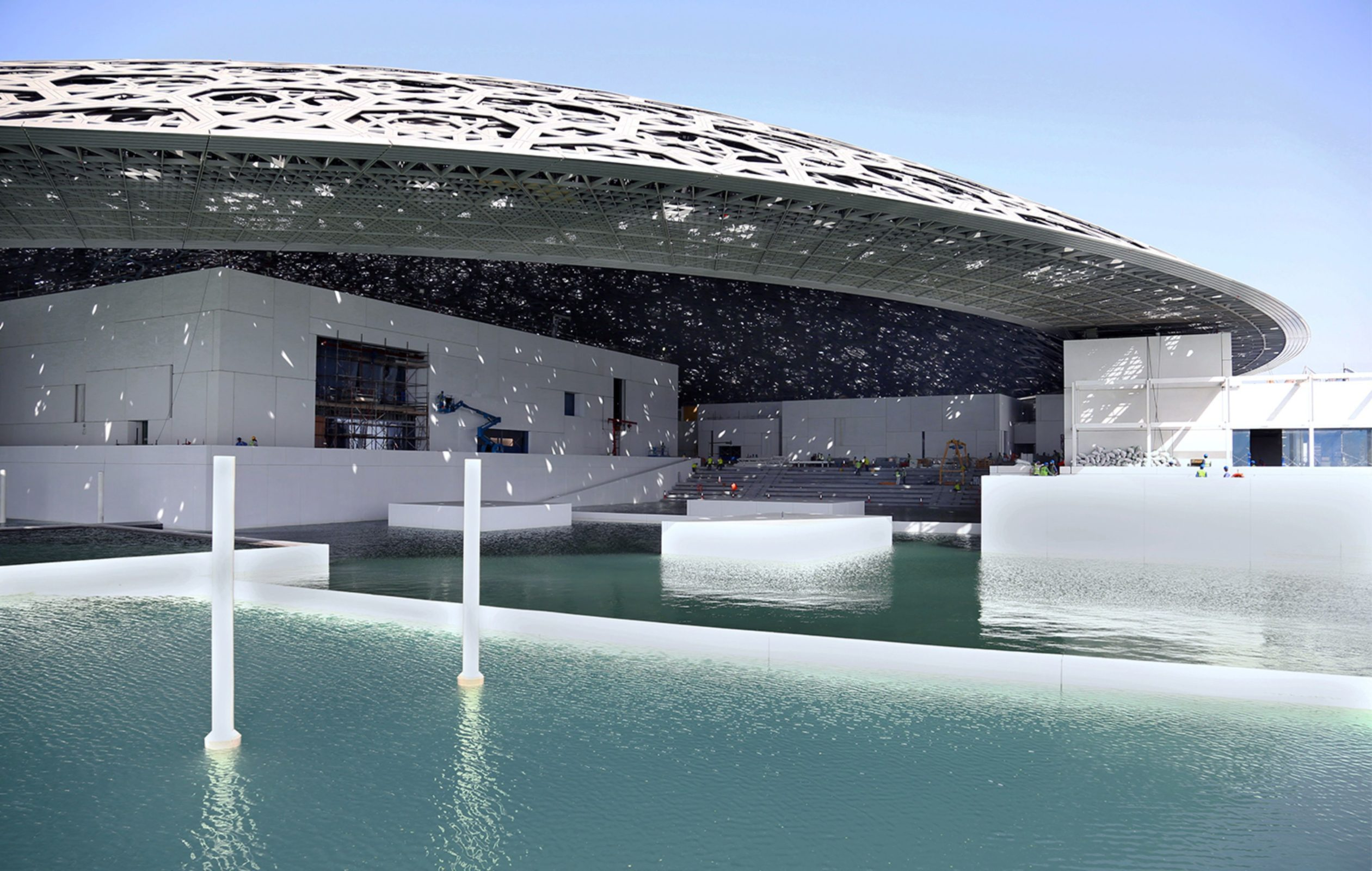 A handout picture taken on May 24, 2016, and made available on June 15, 2016, by Abu Dhabi's Tourism Development and Investment Company (TDIC) shows Abu Dhabi's Louvre museum, designed by French architect Jean Nouvel, surrounded by sea water. The museum has been surrounded by sea water in a major step towards completion of the ambitious project, TDIC said on June 15, 2016. The contractor has begun removing temporary sea protection walls used during the main construction phase, allowing the